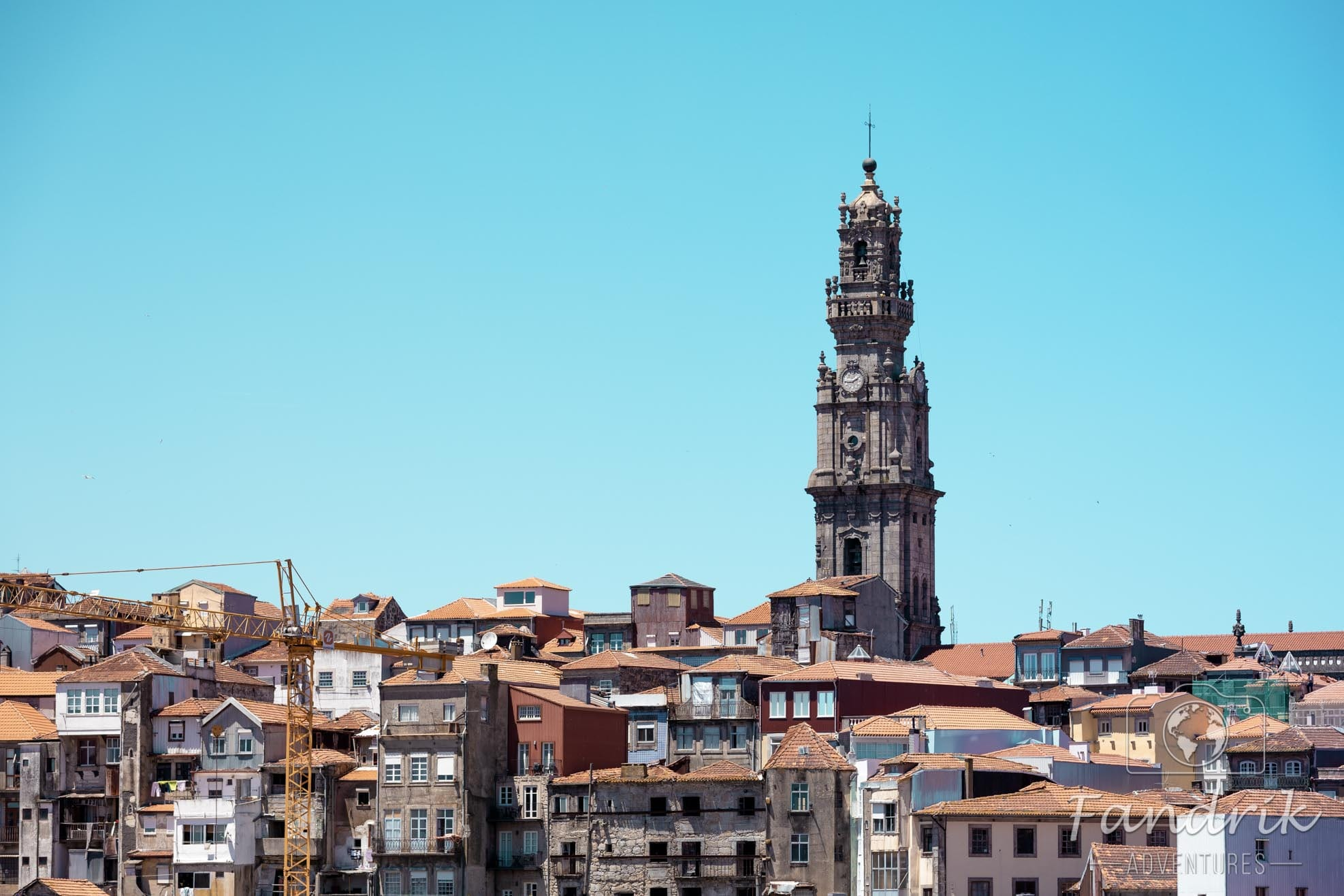 View of the red roofs of Porto with a high tower in the background with a light blue sky